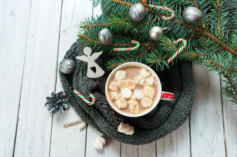 A cup of hot cocoa or chocolate with marshmallows on a background of a knitted scarf and a branch of a Christmas tree. A tradition royalty free stock photo