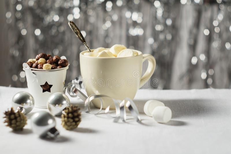 A cup of cocoa with marshmallows and corn balls in the New Year Christmas table setting on a shiny background stock images