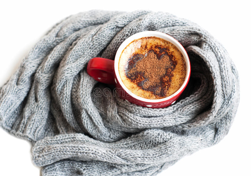 Cup of cocoa wrapped in grey scarf. On a white background stock photography