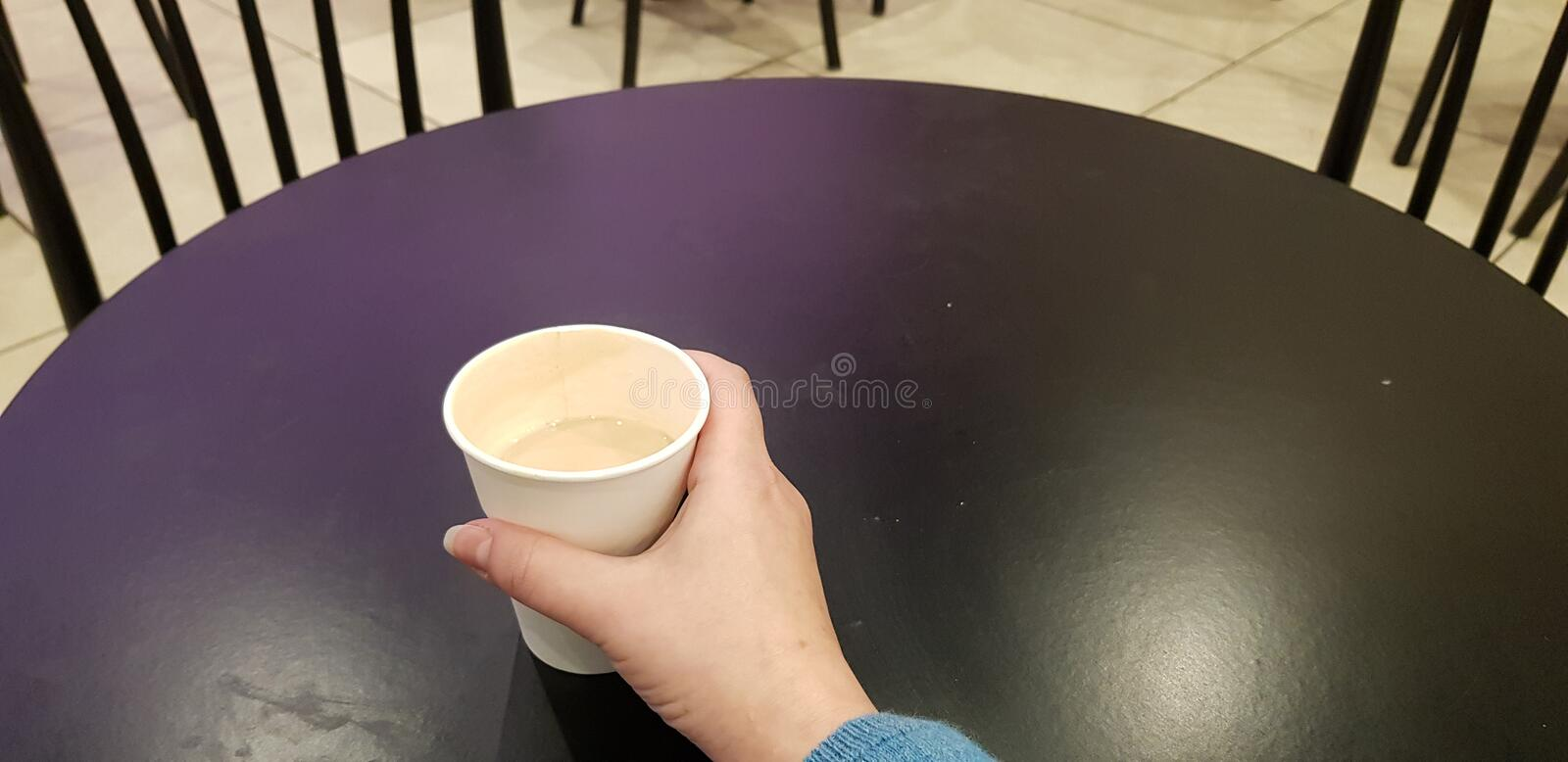 Cup of coffee in female hand on black table. Paper cup of coffee in female hand on black table with two empty chairs waiting for business meeting royalty free stock image