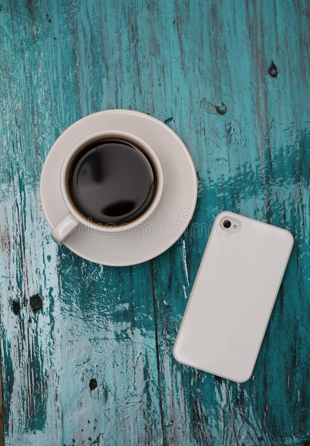 Cup of cofee and phone on tiffany wood background. Flatlay with cup of cofee and phone on turquoise background royalty free stock images