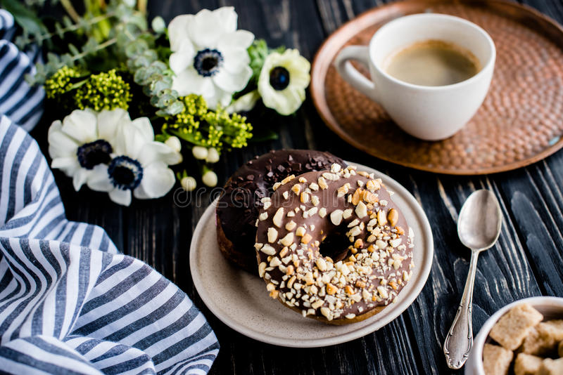 Cup of coffe and a chocolate donuts on black wood royalty free stock photography