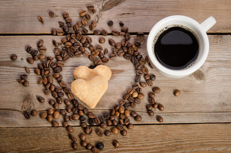 The cup of coffe and Frame- heart from coffee beans and two cook stock images