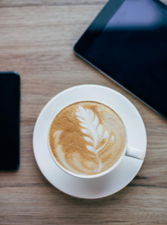 Cup of coffe with latte art standing on the wooden surface with smartphone and  tablet. royalty free stock images