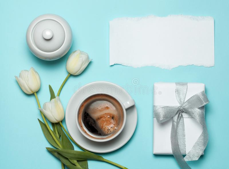 Cup of coffe and white tulips on blue background. stock photography