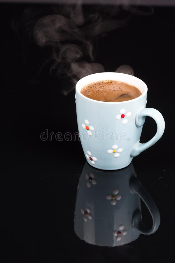 Cup of coffee above black background with reflections royalty free stock photo