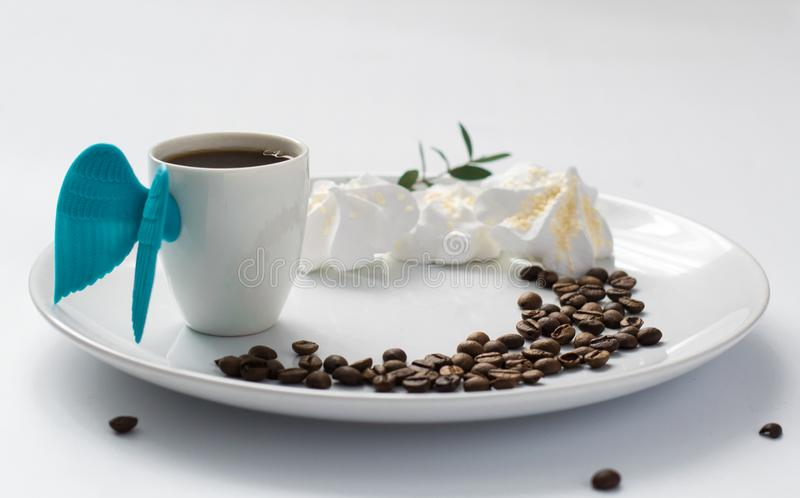Cup coffee angel wings meringue beans plate white blossom espresso morning breakfast light royalty free stock image