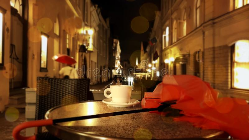 Cup of coffee Autumn evening in city street cafe on table rainy night pink umbrella Old Town Of Tallinn. Autumn leaves  evening in city street cafe cup of coffee royalty free stock photo