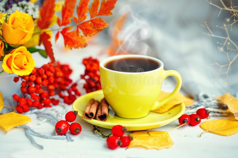 Cup of coffee, autumn leaves and flowers on a wooden table. Autumn still life. Selective focus. stock photography