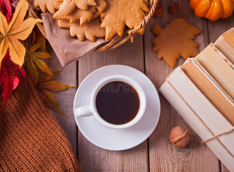 Cup of coffee, autumn leaves, pumpkin, cookies, books on the wooden table. Autumn harvest. Autumn concept. Top view stock photography