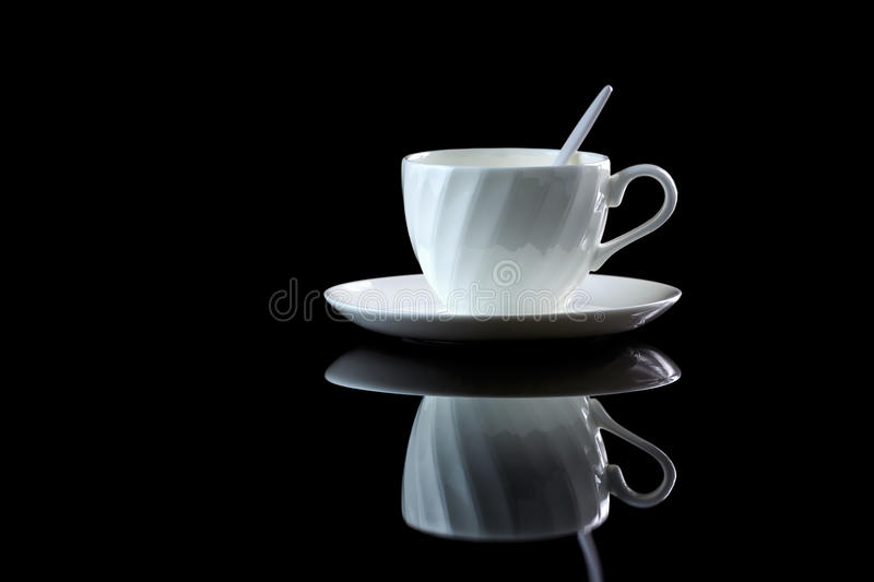 Cup of coffee with backlight on black reflective background. Cup of coffee with backlight on a black reflective background. Studio shot royalty free stock photography