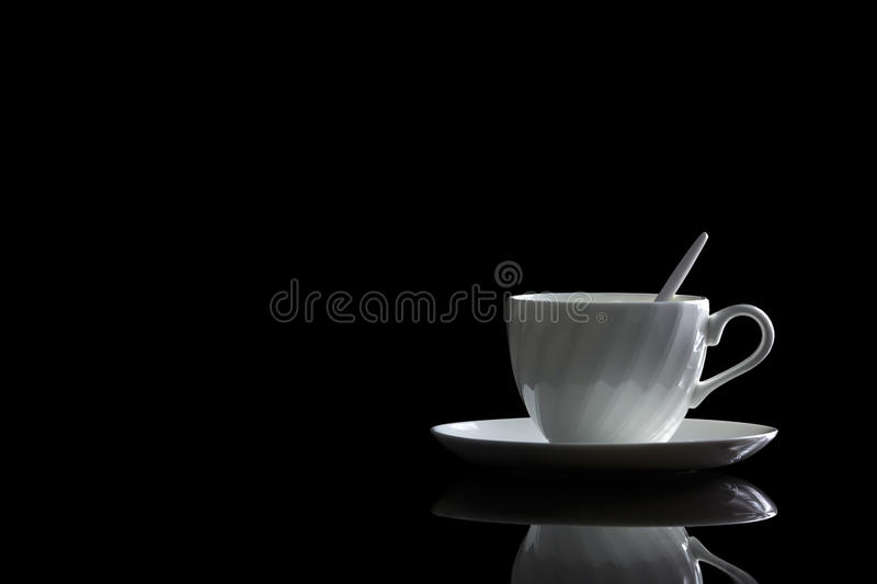 Cup of coffee in backlight on a black reflective background. Studio shot royalty free stock photos