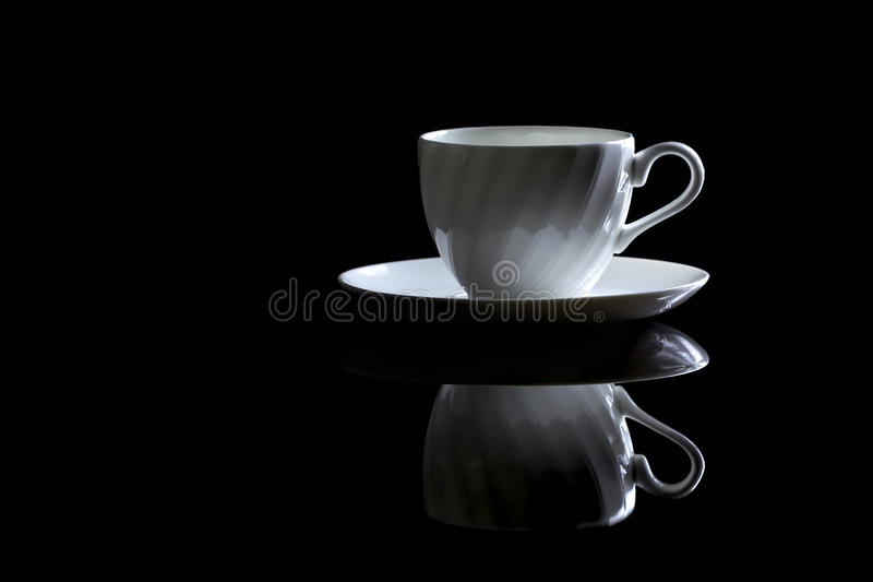Cup of coffee in backlight on a black reflective background. Studio shot royalty free stock images