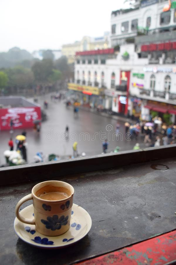 Cup of coffee on balcony table with the city in the background royalty free stock image