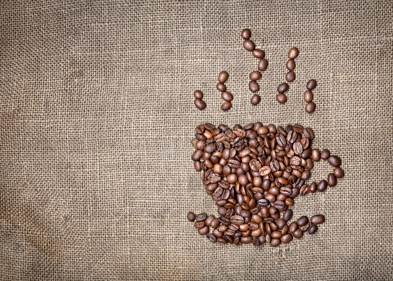 Cup of coffee from beans. Cup of coffee with steam made from coffee beans on textured brown sack. Free space for your text royalty free stock photos