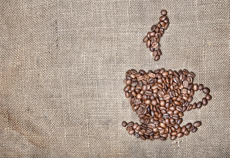 Cup of coffee from beans. Cup of coffee with steam made from coffee beans on textured brown sack. Free space for your text royalty free stock images