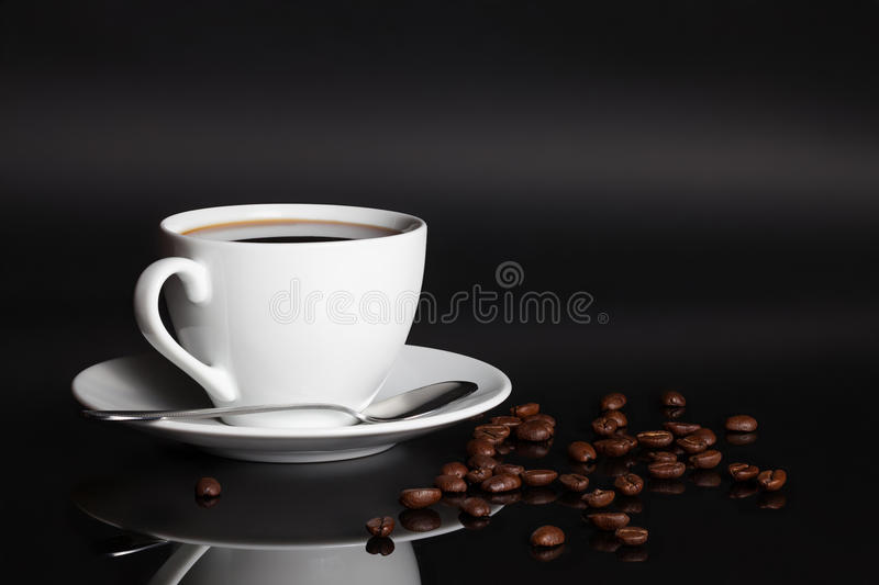 Cup of coffee with beans. Cup of coffee with scattered dry roasted beans reflected on black background royalty free stock images