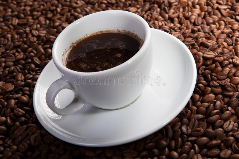 White cup of coffee at coffee beans backgrounds royalty free stock image