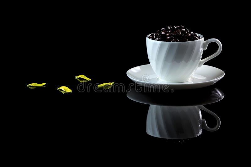 Cup with coffee beans on a black reflective background. Studio shot stock photo