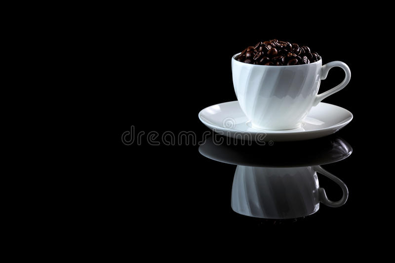 Cup with coffee beans on a black reflective background. Studio shot royalty free stock image