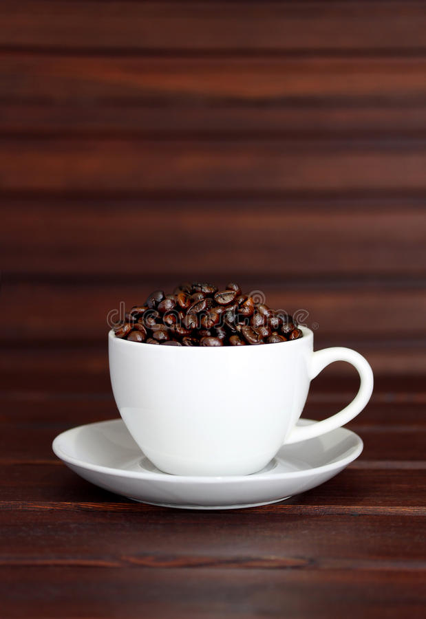 Cup of coffee. Beans on brown wood background stock photos