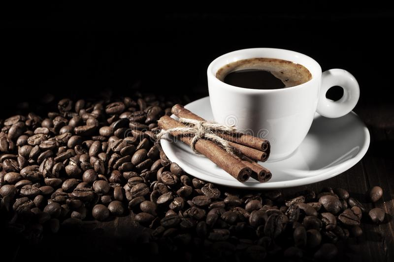 Cup of coffee with coffee beans and cinnamon sticks stock image