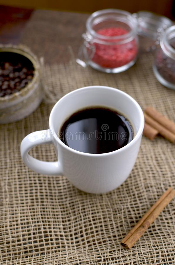 A cup of coffee, coffee beans, cinnamon sticks, a sweet chocolate ingredient in a jar royalty free stock image
