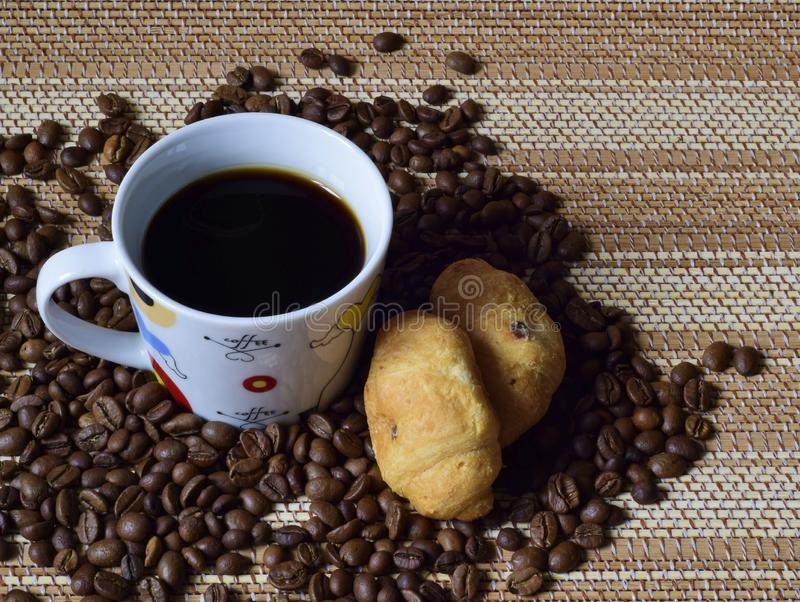 A Cup of coffee beans and croissants. stock photos