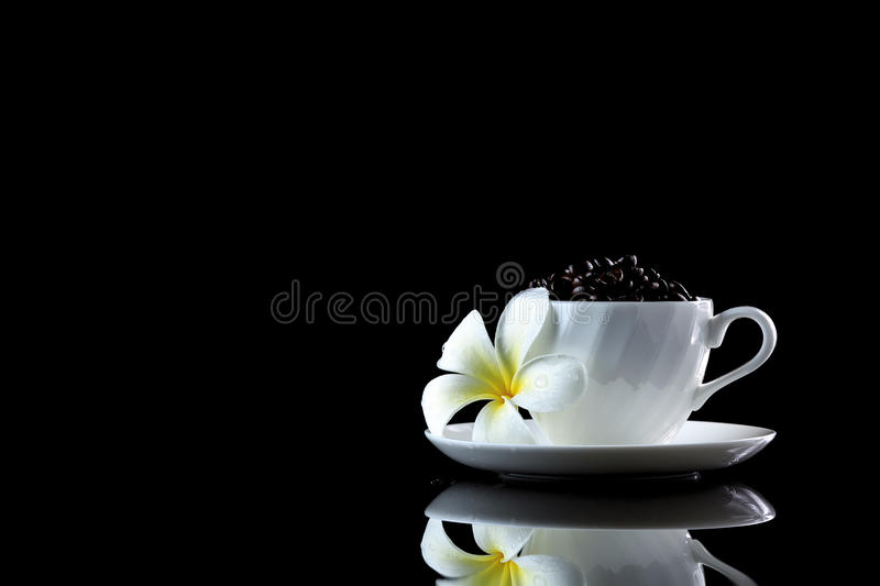 Cup with coffee beans and frangipani on a black reflective backgr. Ound. Studio shot stock photo