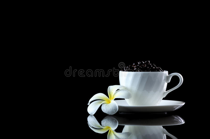Cup with coffee beans and frangipani on a black reflective backgr. Ound. Studio shot royalty free stock photo