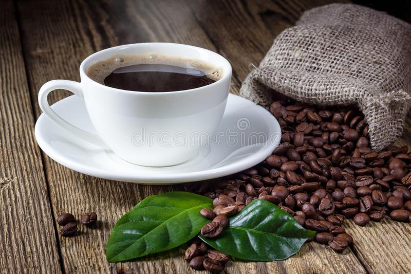 Cup of coffee, beans and leaf. On wooden rustic table stock photo