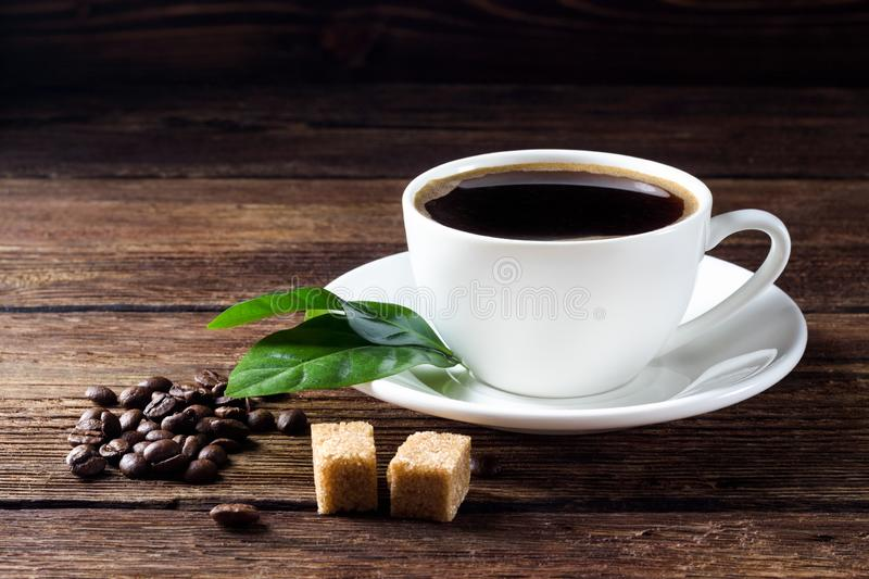 Cup of coffee with beans, leaf and sugar stock photos
