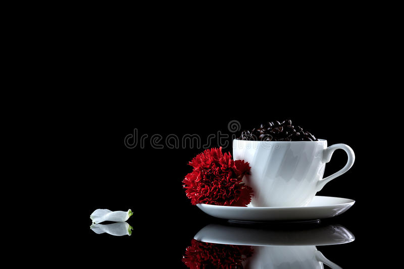 Cup with coffee beans and red carnation on a black reflective bac. Kground. Studio shot royalty free stock photography