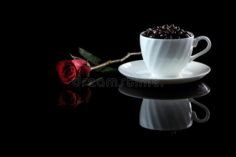 Cup with coffee beans and rose on a black reflective background. Studio shot stock images