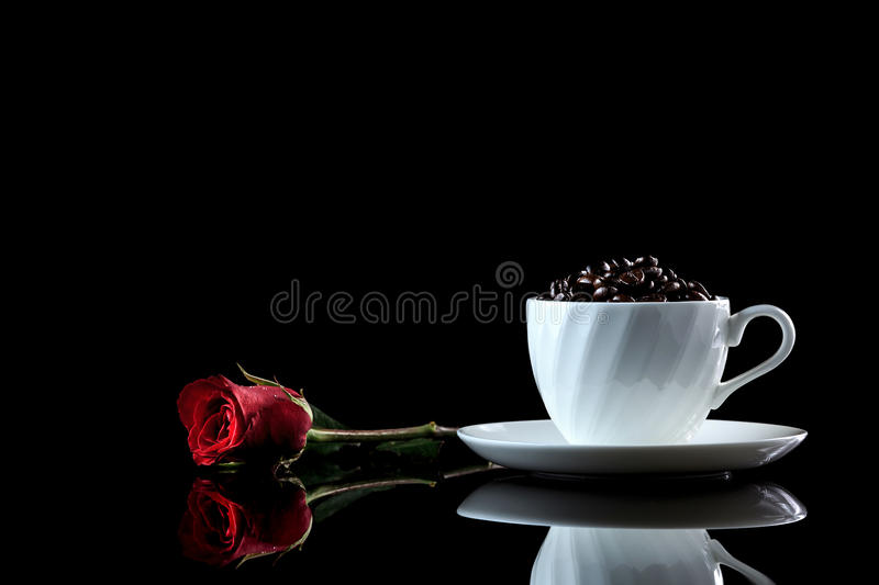 Cup with coffee beans and rose on a black reflective background. Studio shot royalty free stock photos