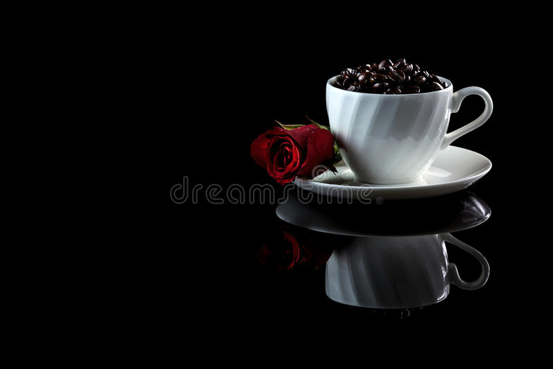 Cup with coffee beans and rose on a black reflective background. Studio shot stock image
