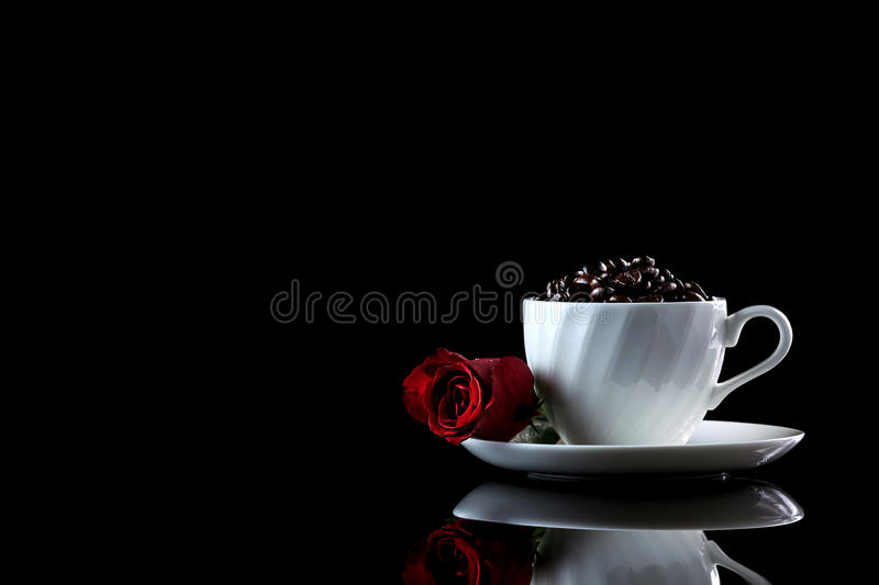 Cup with coffee beans and rose on a black reflective background w. Ith backlight. Studio shot royalty free stock photo