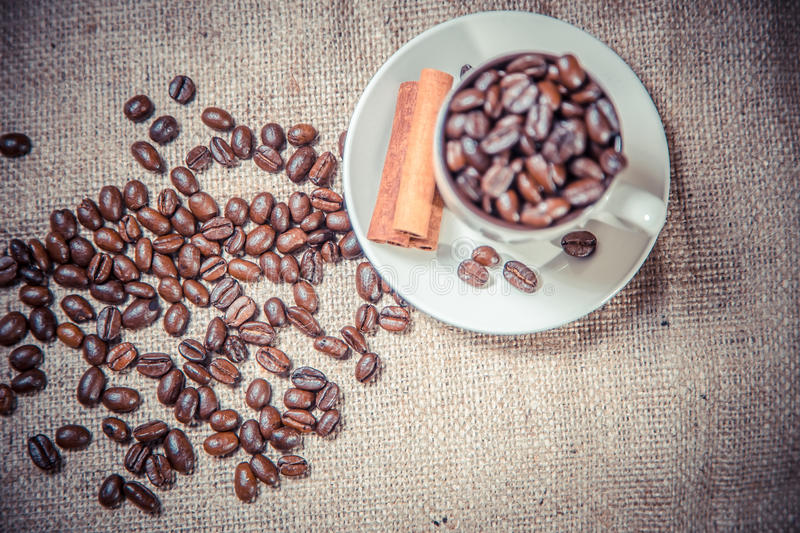 Cup of coffee beans on sackcloth royalty free stock image