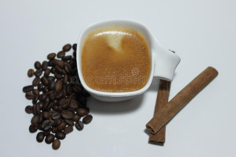 Cup of coffee, beans and two sticks of cinnamon stock images