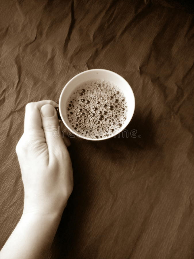 Cup of coffee. On a beautiful gothic background a woman snow-white hand retains the glossy ceramic cup of magnificent fragrant coffee. Coffee drink is covered stock image
