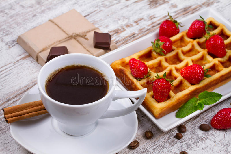 Cup of coffee, Belgium waffle and strawberries. Cup of coffee, Belgium waffle and strawberries stock photography