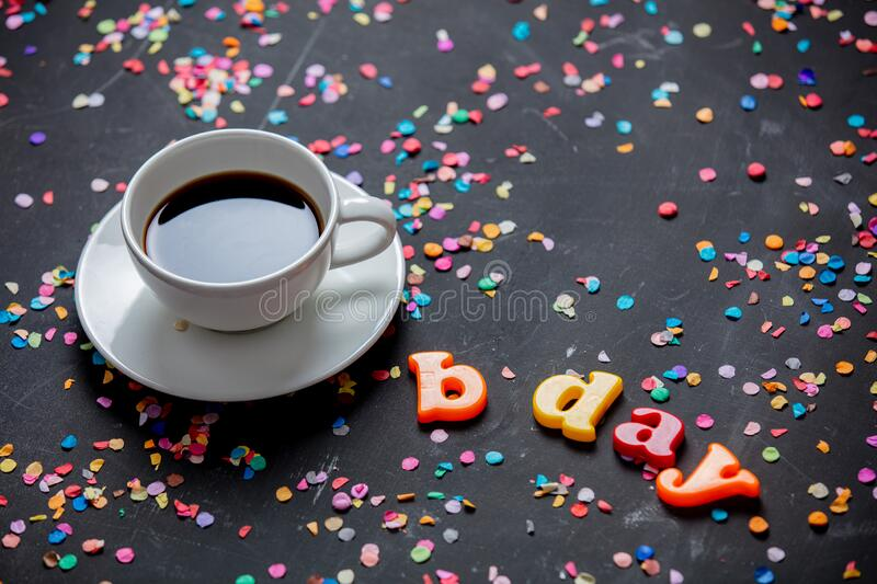 Cup of coffee and Birthday letters with confetti stock photography