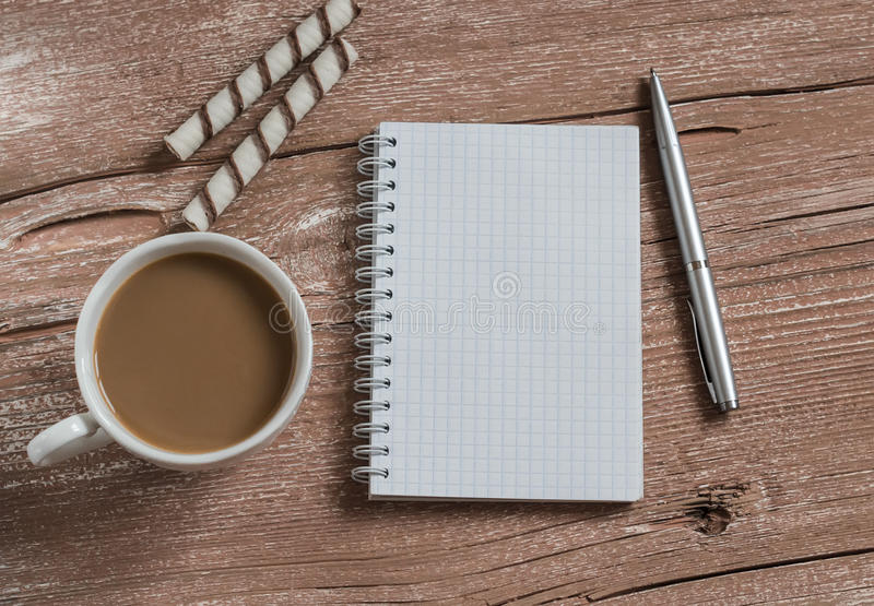 Cup of coffee, biscuits and a blank open notebook on a wooden table.Top view. stock images