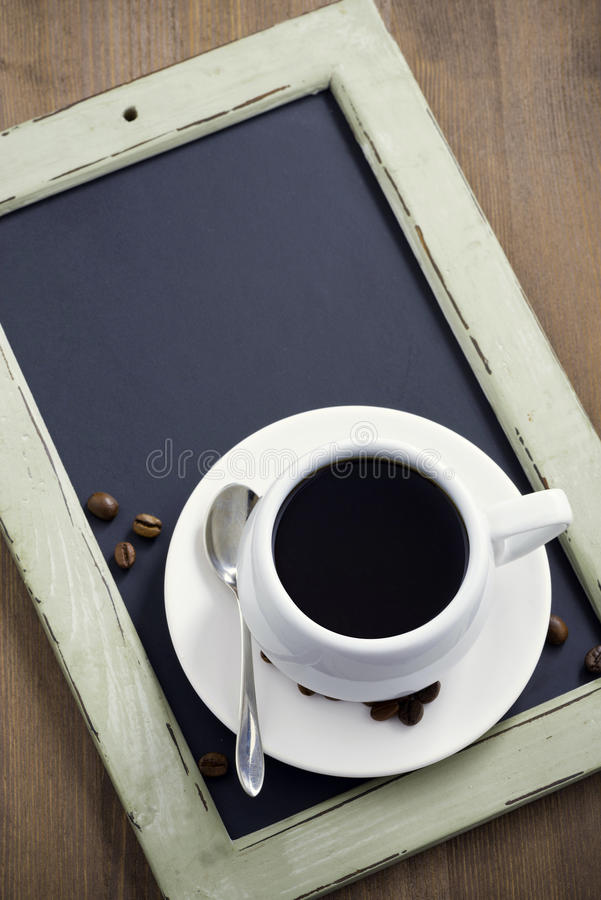 Cup of coffee on black chalkboard, top view, vertical royalty free stock images