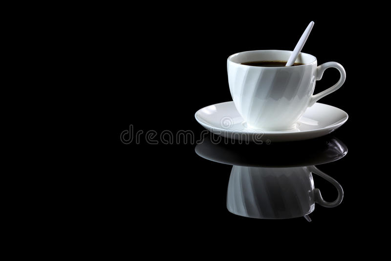 Cup of coffee on a black reflective background. Studio shot stock image