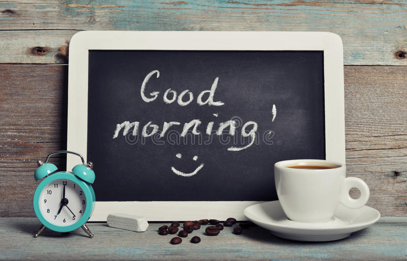 Cup of coffee with blackboard. And alarm clock on vintage wooden background royalty free stock images