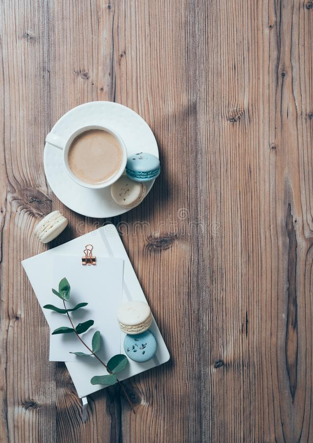 Cup of coffee and blue macaroons on wooden table background royalty free stock images