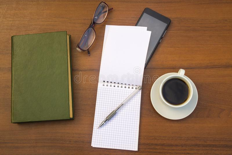 Cup of coffee, book, notepad, pen, eyeglasses and smart phone on desk stock photography