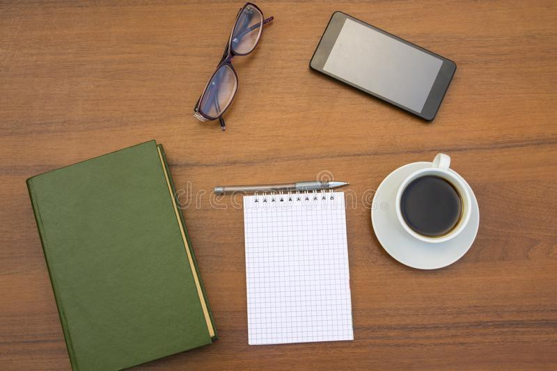 Cup of coffee, book, notepad, pen, eyeglasses and smart phone on wooden desk stock photos
