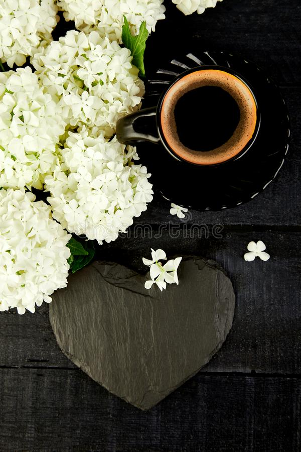 Cup of coffee with bouquet hydrangea Good morning. Flat. Valentine Day. Cup of coffee with bouquet flower hydrangea and slate heart on black wooden background royalty free stock photography
